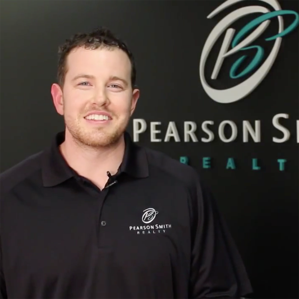 Eric Pearson wearing Polo Shirt Style T475 in black with the Pearson Smith Realty logo embroidered on the left chest