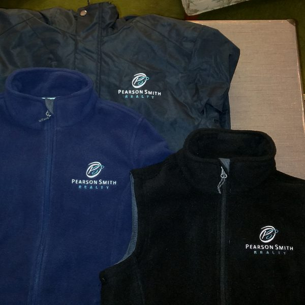 Navy Fleece Style L217, Black Vest Style L219, and Black Jacket Style J331 each embroidered with the Pearson Smith Realty logo on the left chest