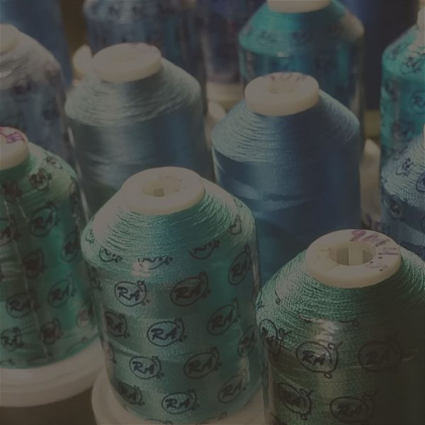 Embroidery threads, on spools, in a variety of blue shades