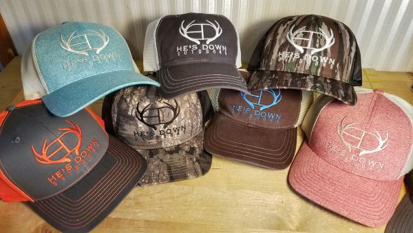 Seven baseball caps each embroidered with the He's Down Outdoors logo
