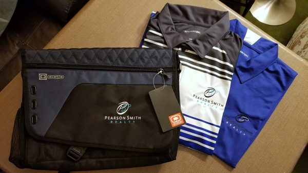 Computer bag and two polos each embroidered with the Pearson Smith Realty logo