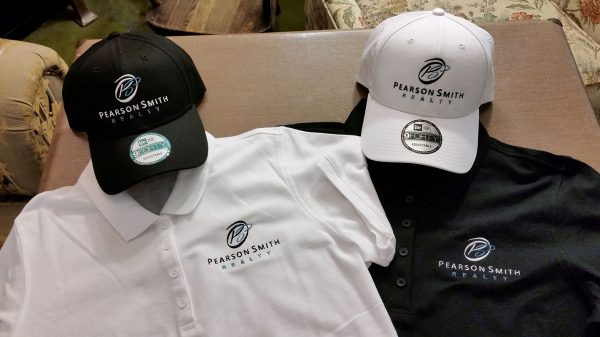 Two polo shirts and two baseball caps each embroidered with the Pearson Smith Realty logo
