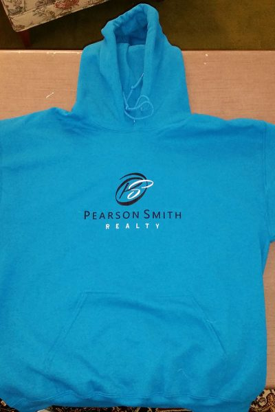 Blue hoodie sweatshirt with the Pearson Smith Realty logo embroidered on the front