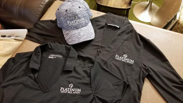 Polo, cardigan and baseball cap each embroidered with Platinum Group Real Estate logo